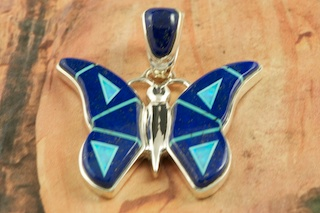 Stunning Butterfly Pendant features Genuine Blue Lapis inlaid in Sterling Silver. Beautiful Fire and Ice Lab Opal Accents. Free 18&quot; Sterling Silver Chain with Purchase of Pendant. Designed by Navajo Artist Calvin Begay. Signed by the artist.